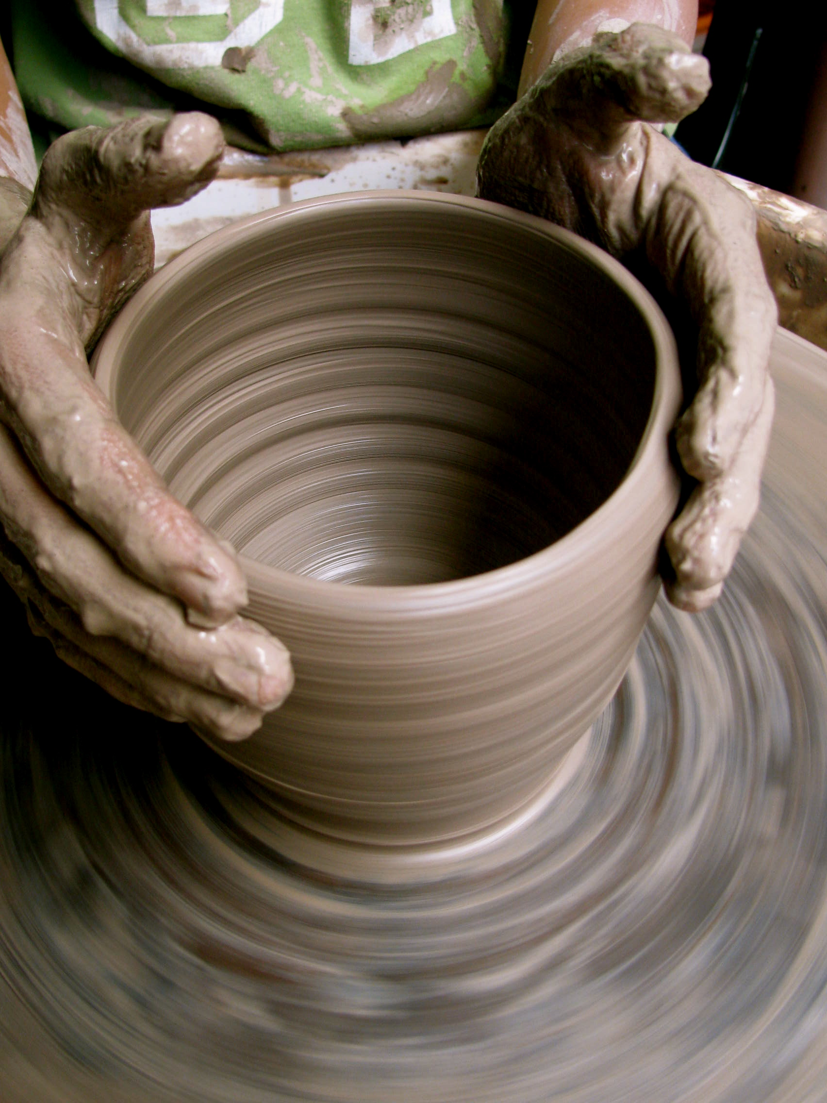 Hands working on a piece of pottery