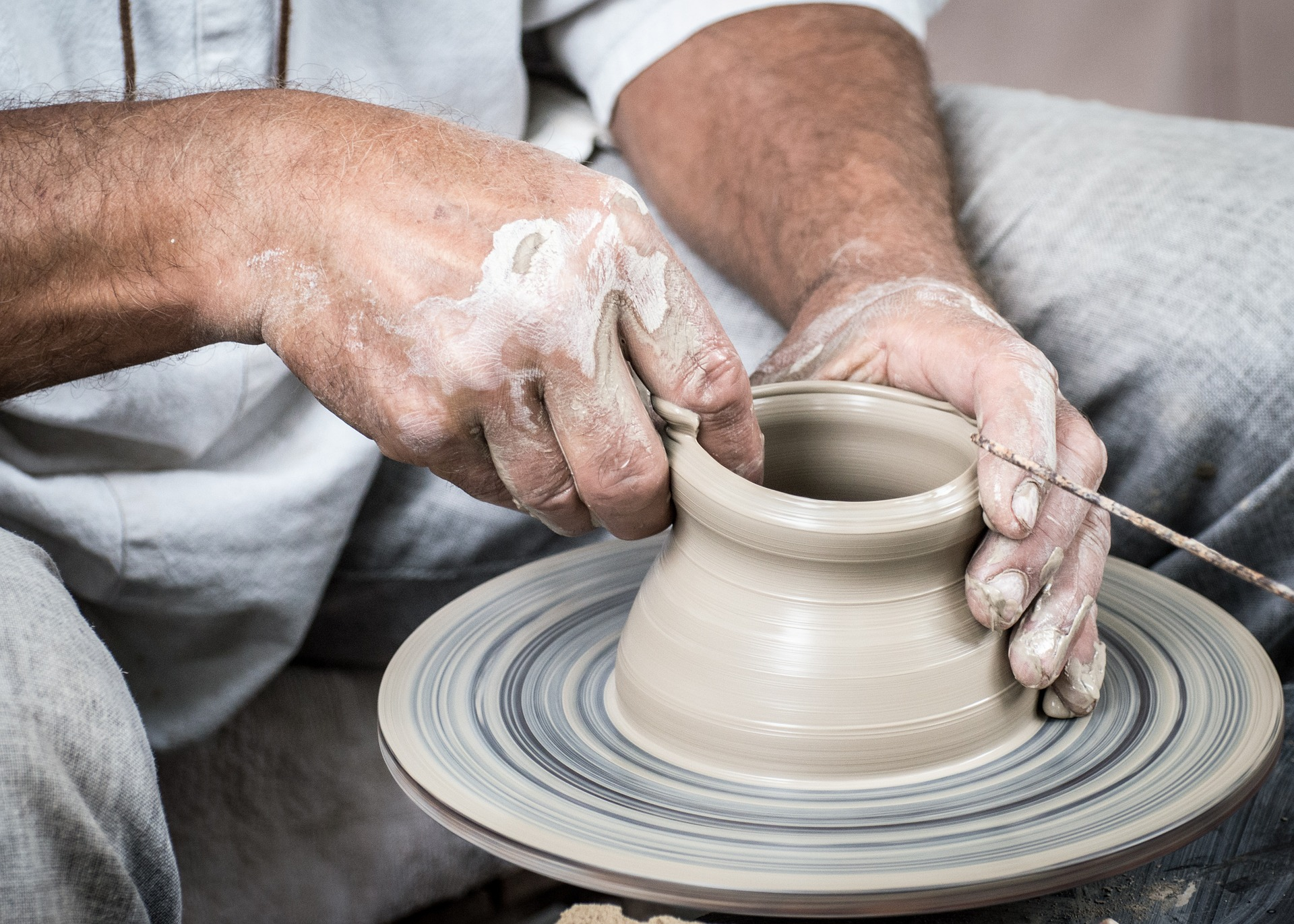 adult making pottery